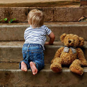 Child climbing steps and a teddy